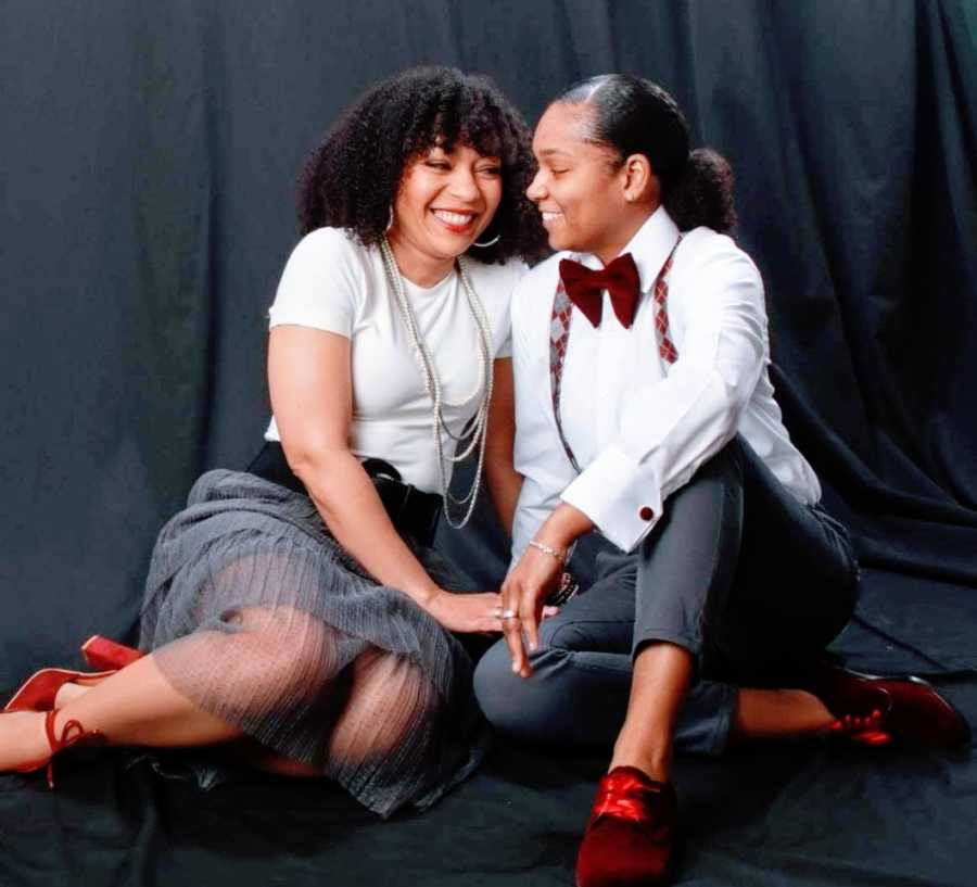 A woman and her wife dressed up against a black background