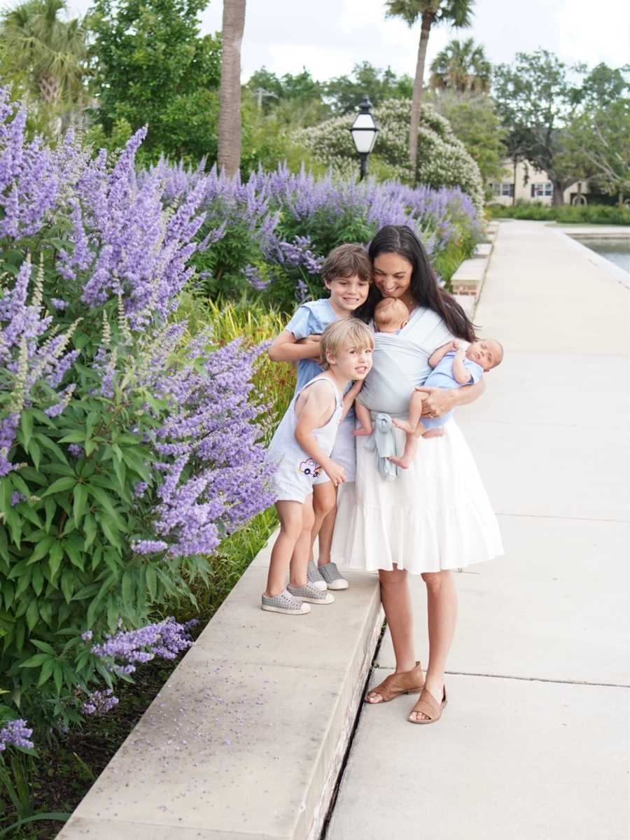 Pregnant mother holding all four children by purple flowers