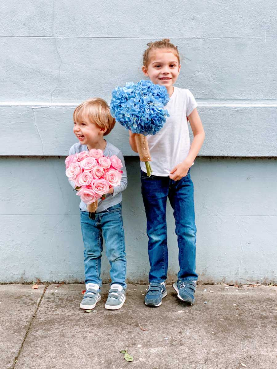 Two brothers holding a pink and a blue bouquet of flowers