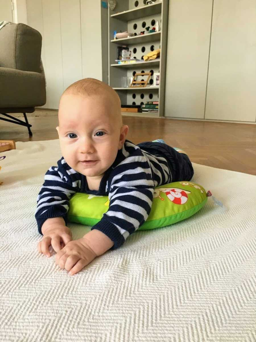 Baby boy lying on carpet