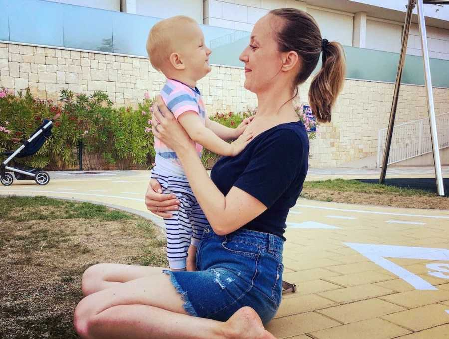 Mom holding son outside and smiling