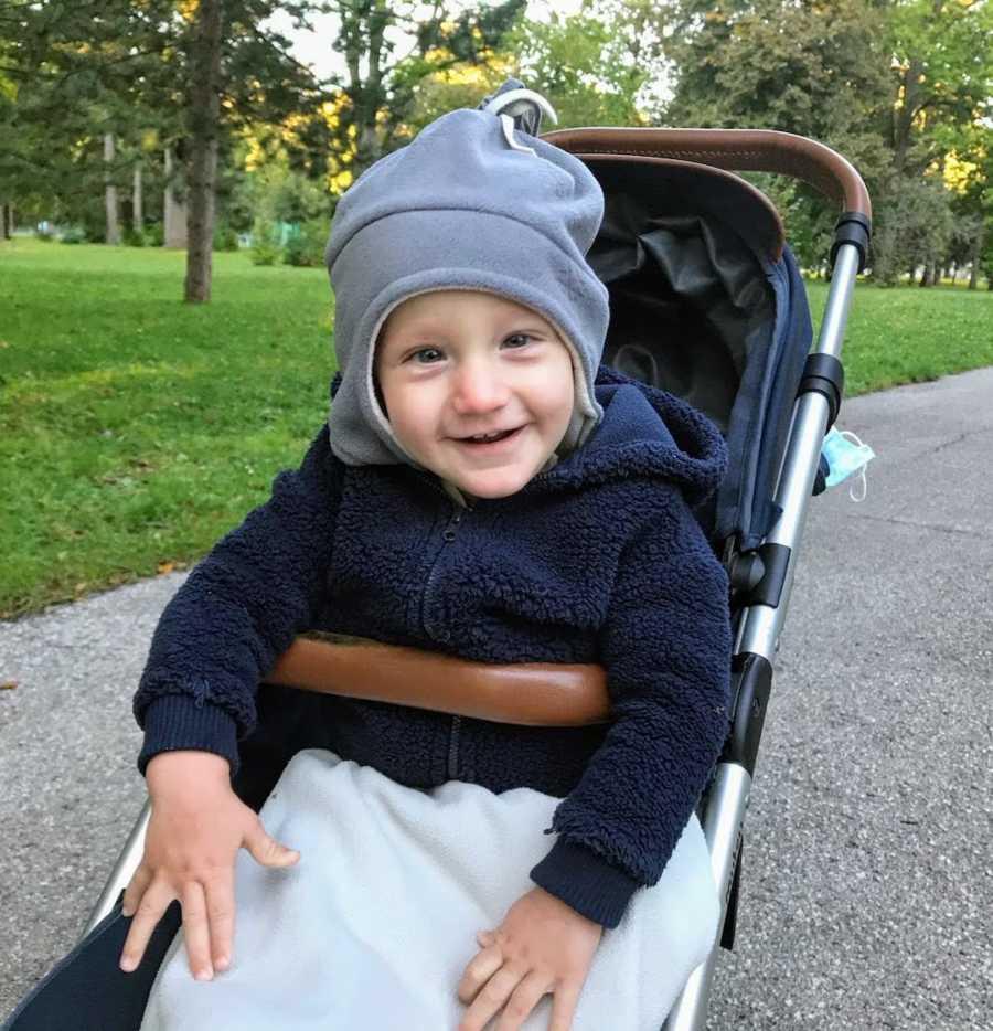 Toddler boy sitting in stroller wearing hat and smiling