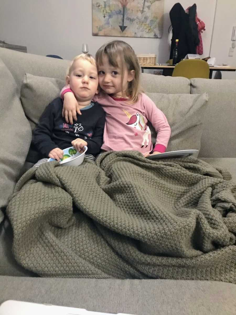 Brother and sister wrapped in blankets on brown couch