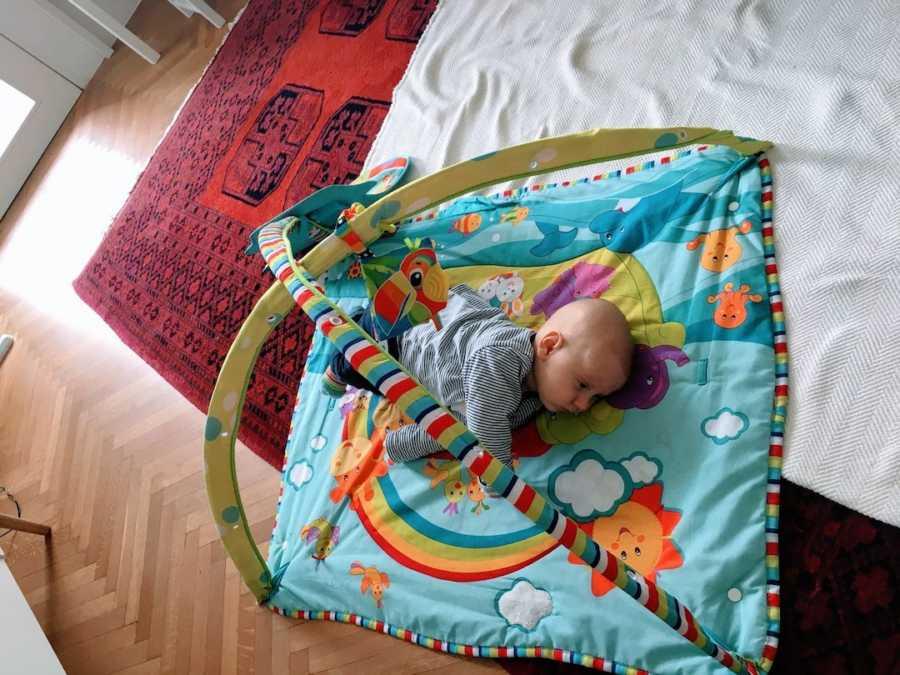 Newborn baby boy lying on playmat
