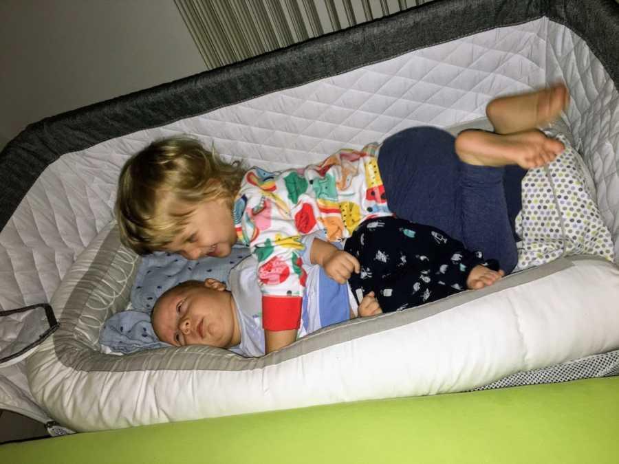 Newborn baby boy lying in crib with big sister