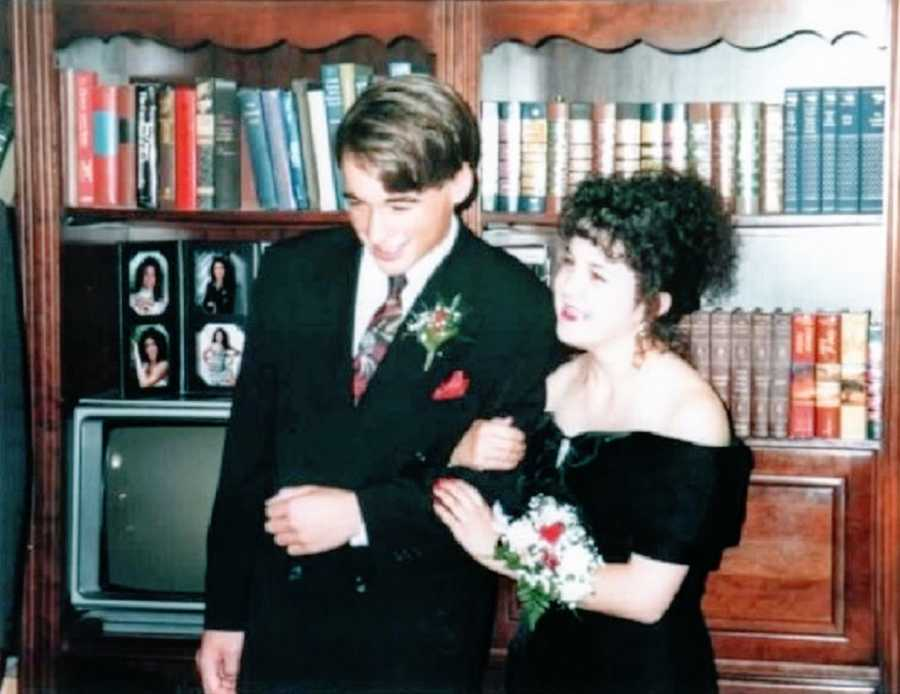 A girl with curly brown hair wears a black dress standing next to her prom date