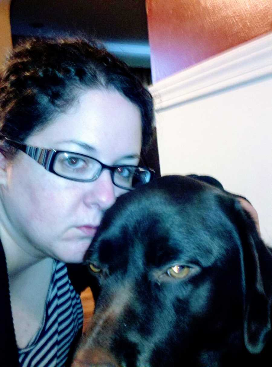 A woman who is struggling with her mental health sits next to a brown dog