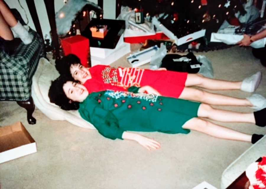 Twin girls lie on the floor together wearing Christmas clothing