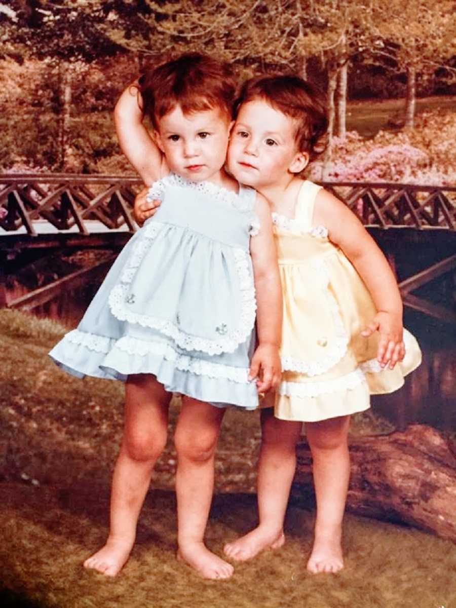 Twin girls wearing dresses hug each other