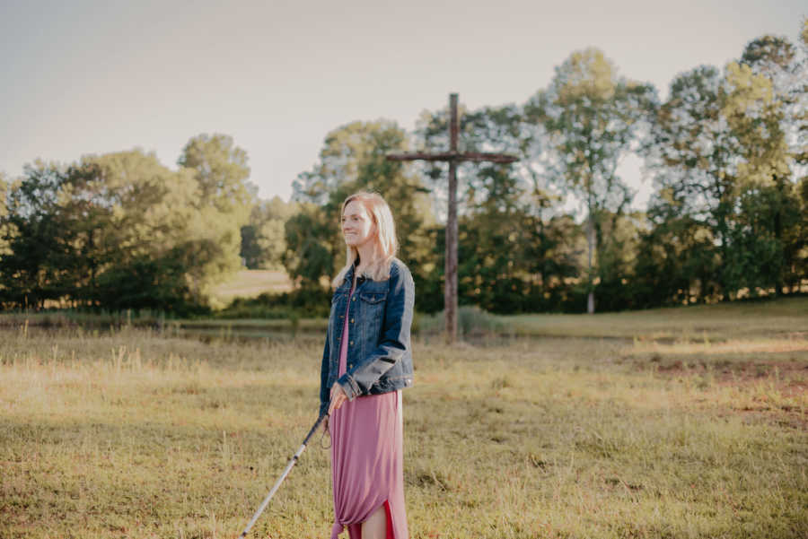 Blind woman using walking cane standing in field with wooden cross