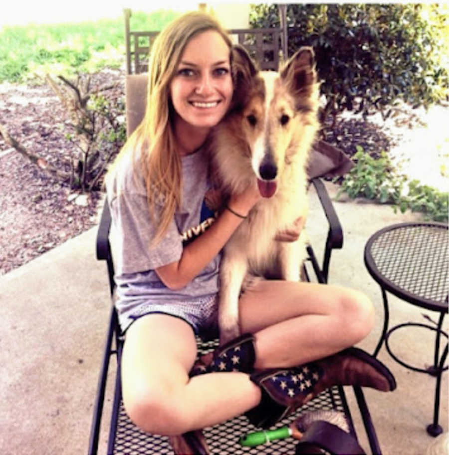 Young blonde woman sitting in metal chair outside on patio with dog