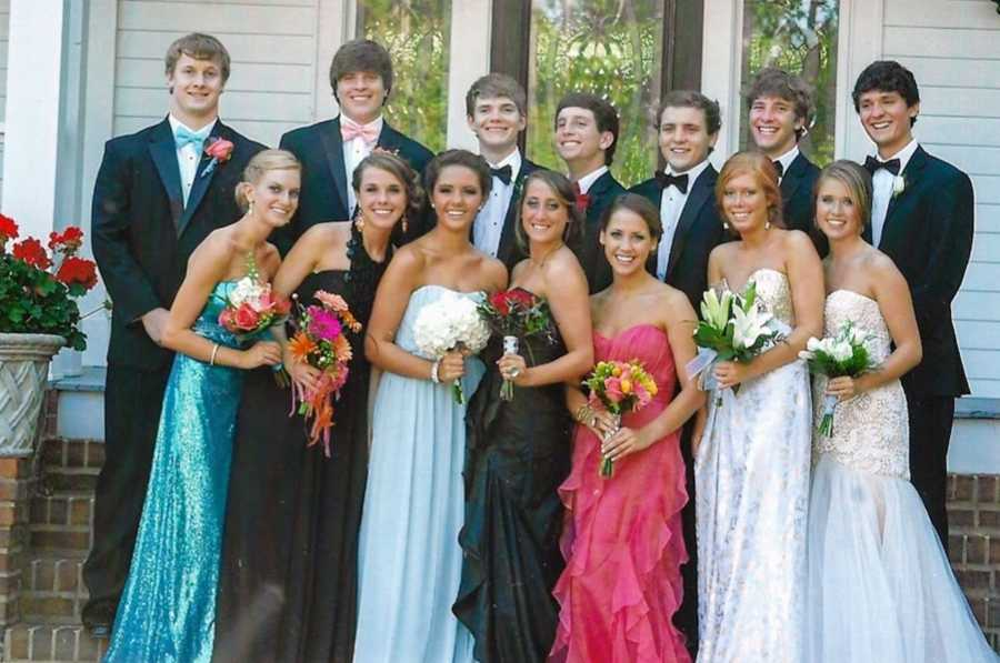 Prom picture of large group of boys and girls where the girls are holding bouquets