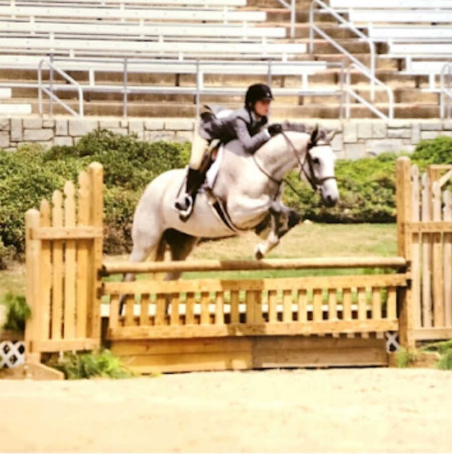 Equestrian doing jump with white horse