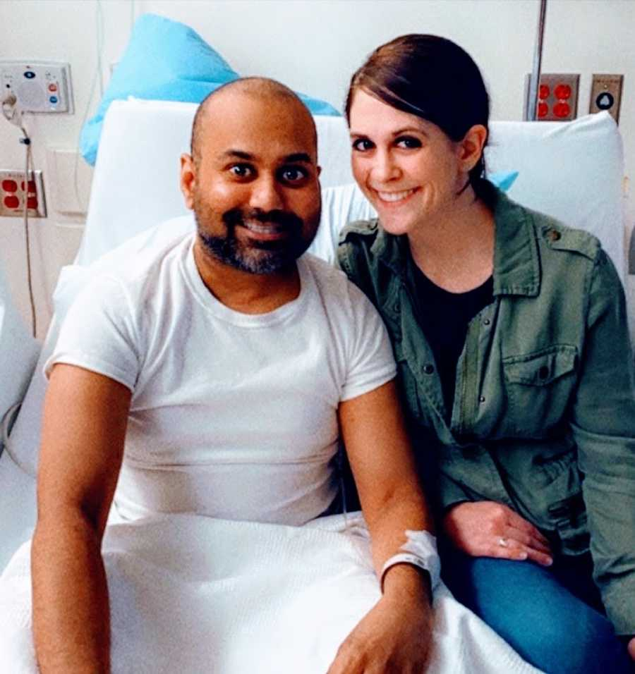 Man in hospital bed with woman smiling
