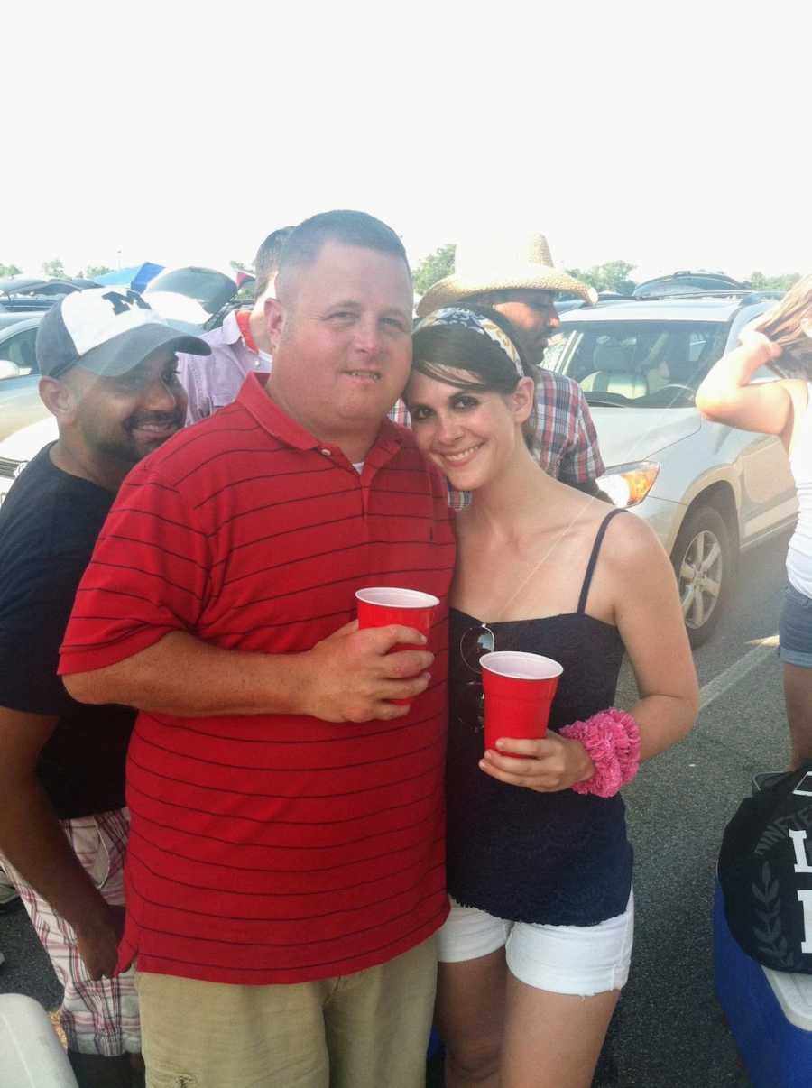Woman and man taking picture at concert holding cups