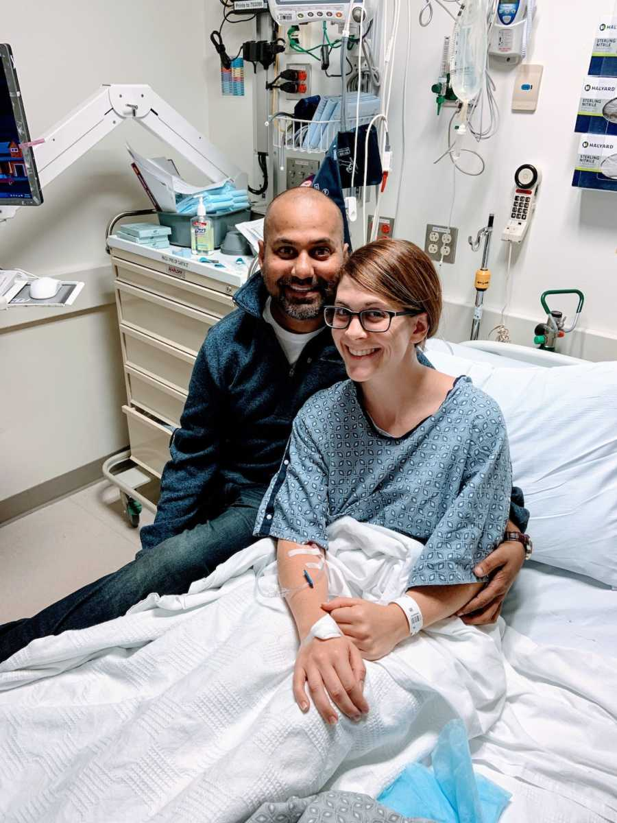 Woman in hospital bed sitting with man