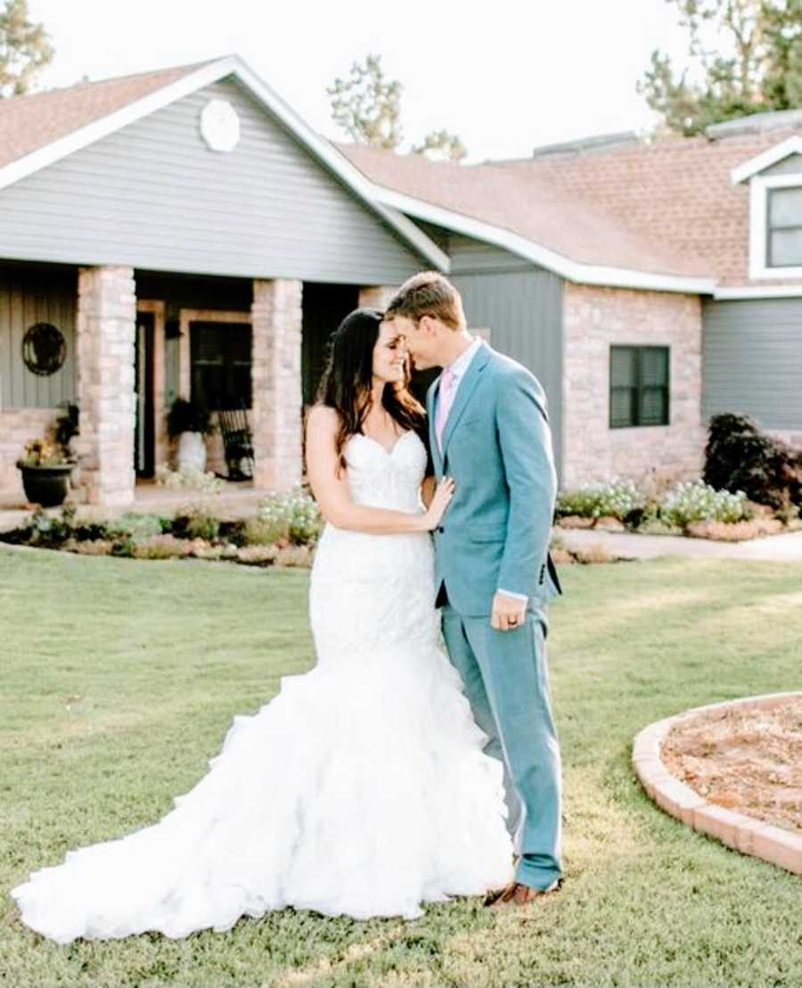 A bride and groom stand together outside their home
