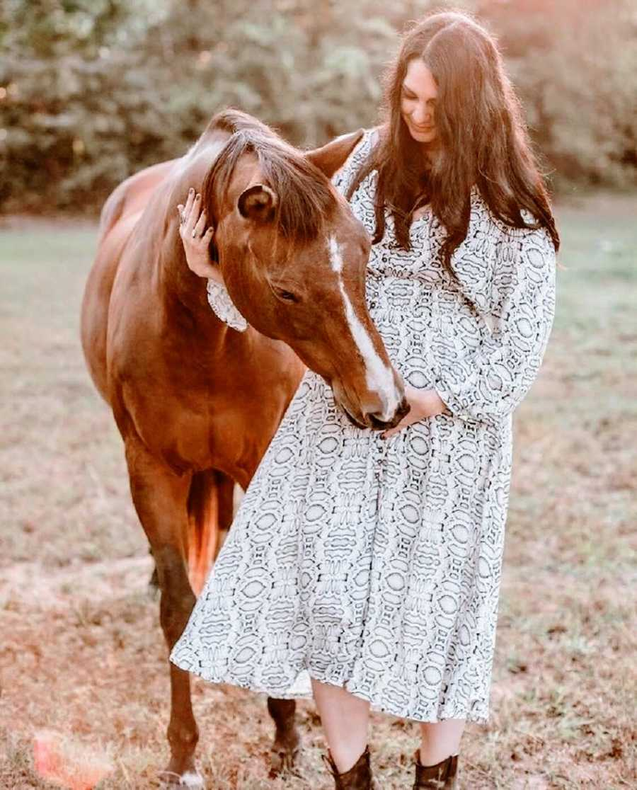 A pregnant woman stands with a brown horse