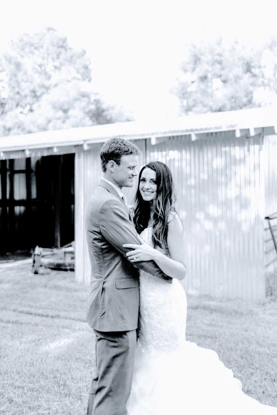 A bride and groom stand together outside a barn