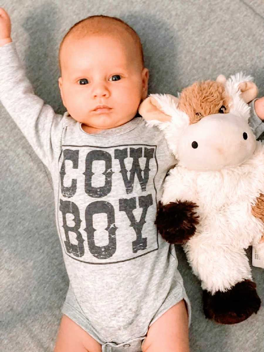 """A baby boy wearing a shirt that says """"Cowboy"""" holds a stuffed cow"""