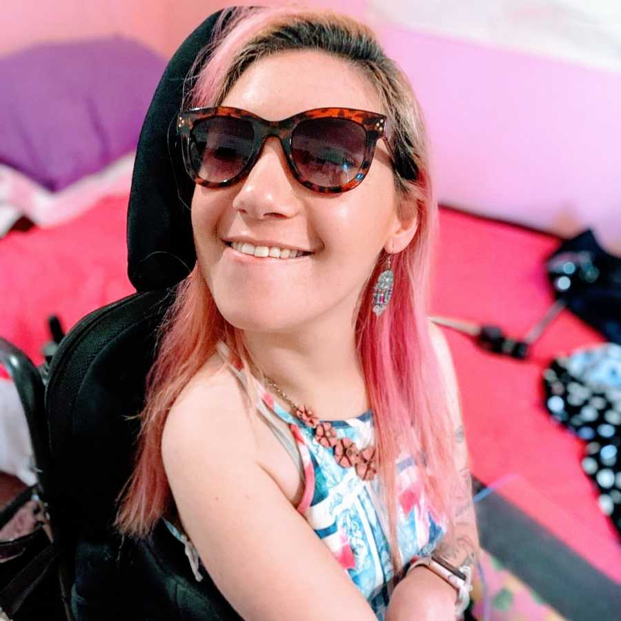 A woman with cerebral palsy and endometriosis wearing sunglasses