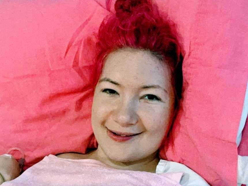 A woman with endometriosis lies on a pink pillow in a hospital bed