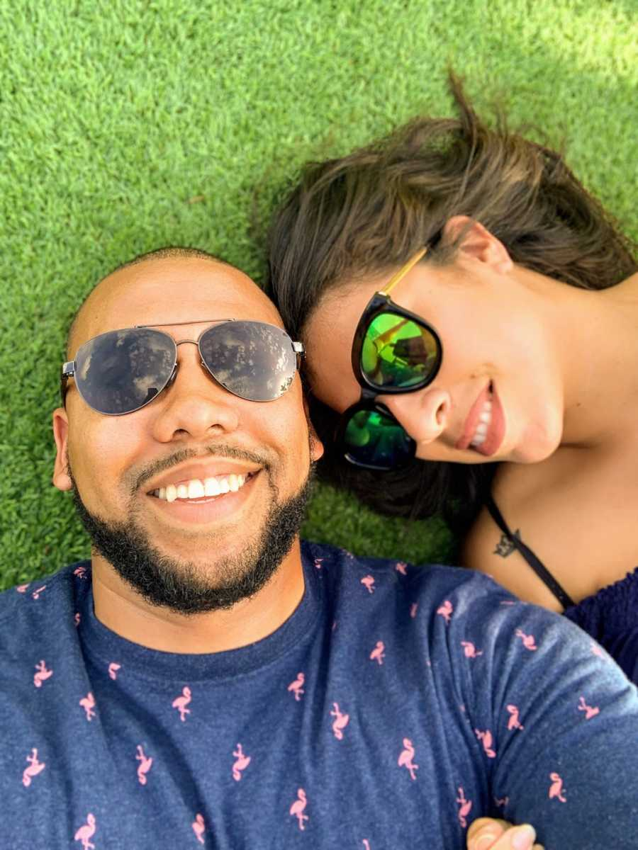 Couple lying on the grass wearing sunglasses taking selfie