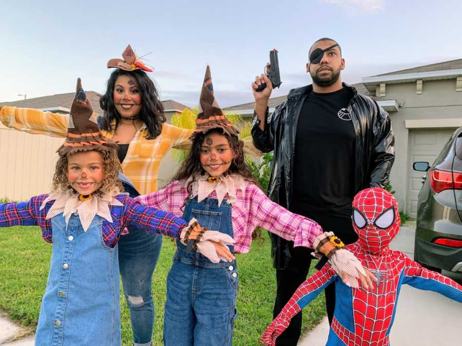 Family dressed in Halloween costumes posing outside