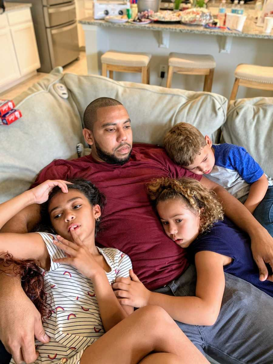 Father lying on couch cuddling with three children