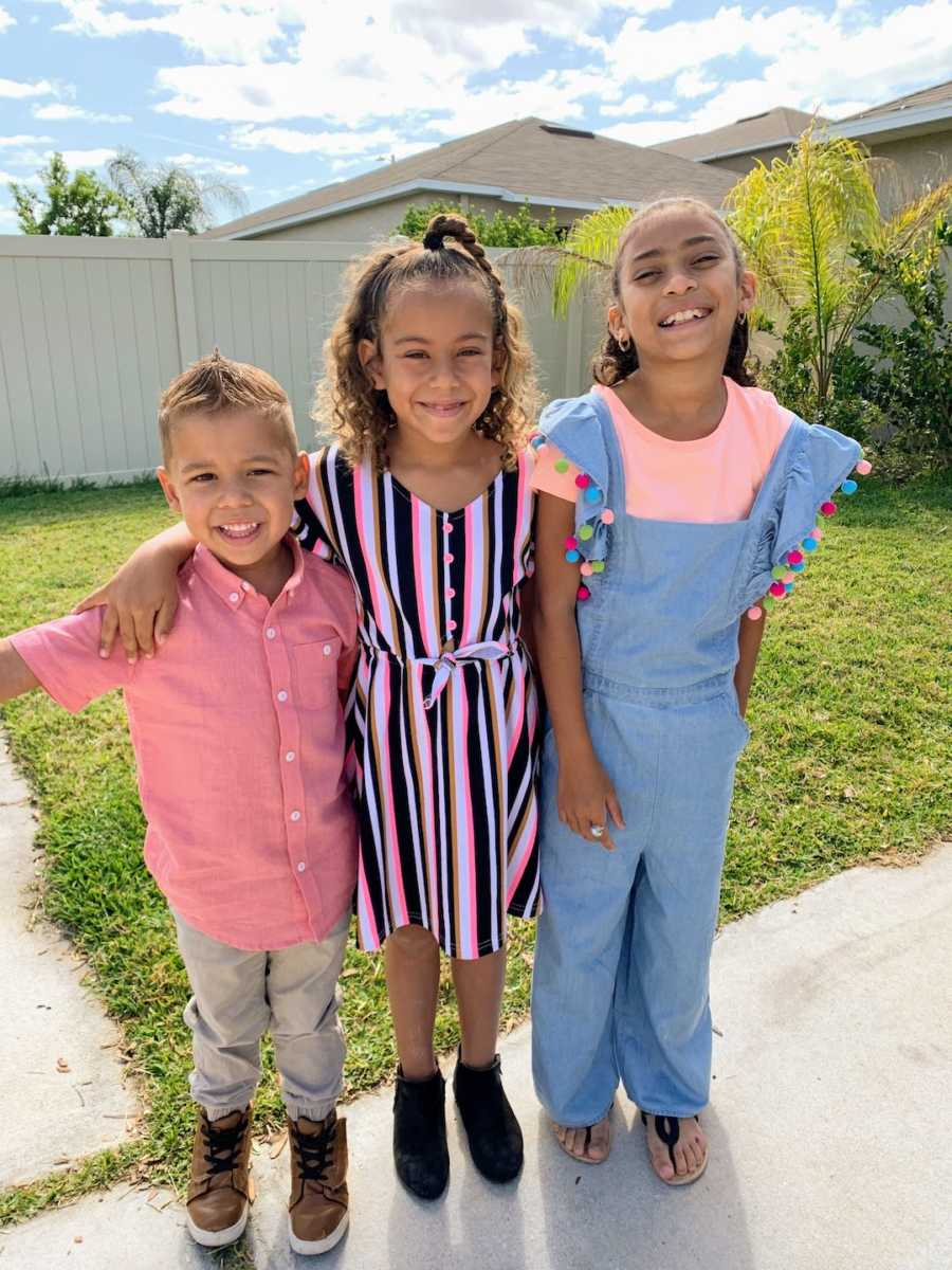 Two sisters standing with arms around their little brother outside