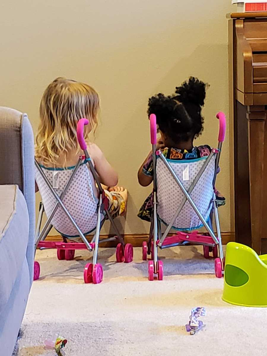 Foster sisters sitting in toy strollers talking