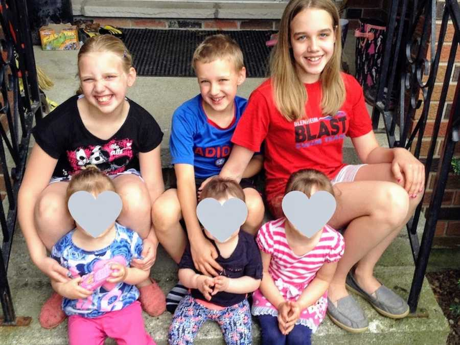 Six foster siblings sitting and smiling on front porch steps