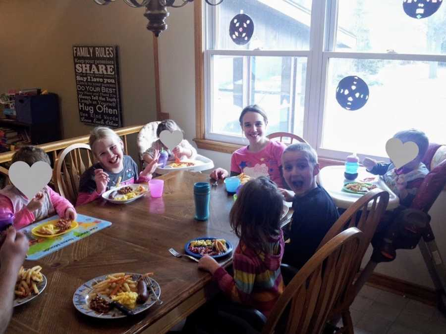 Large group of foster siblings sitting at kitchen table smiling
