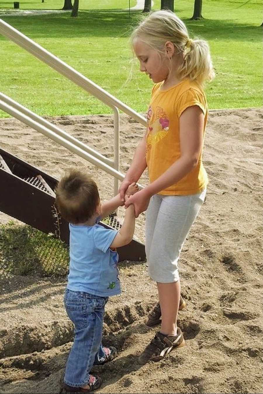 Foster siblings holding hands at playground