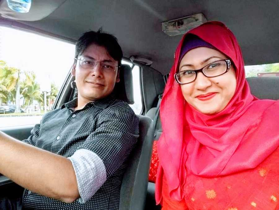 A woman in a red hijab and her husband sit in a car