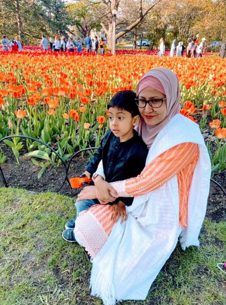 A neurodivergent mom holds her autistic son near flowers at a park