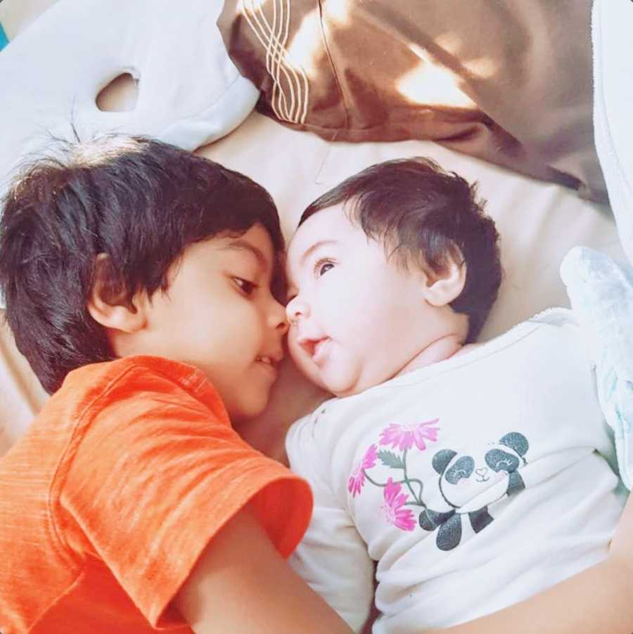 An autistic boy and his baby sister lie close together