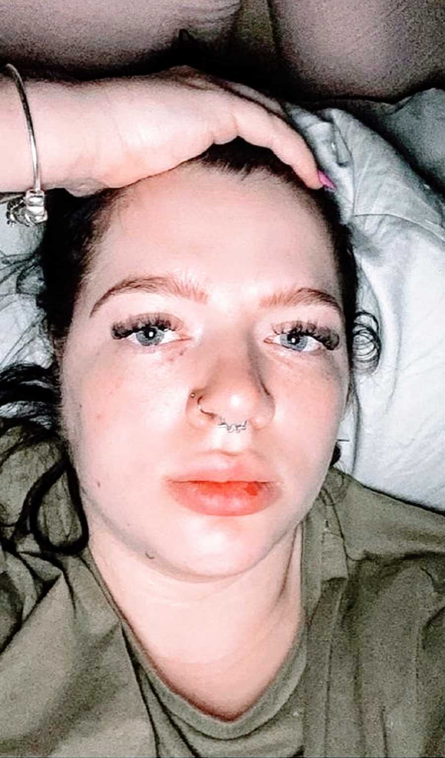 A woman with nose piercings lies uncomfortably in bed