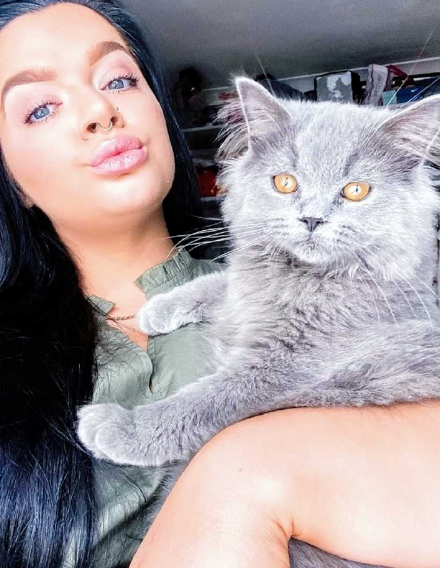 A woman with chronic illness holds a grey cat in her lap