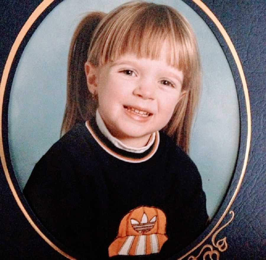 A young girl in a sweater for her school photo
