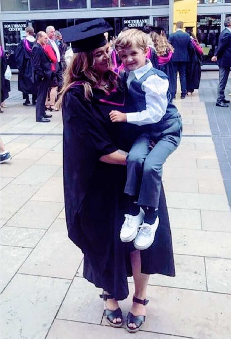 A woman with chronic illness holds her son at a graduation