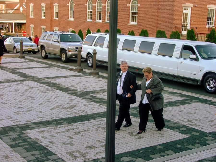 Brother and sister walking on street with white limo in background