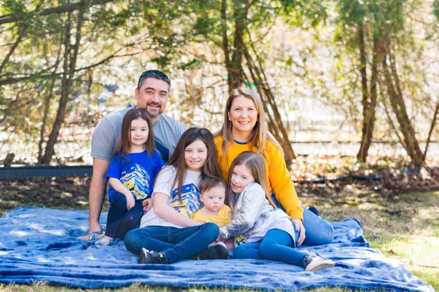 Family of 6 sitting on blue blanket outside