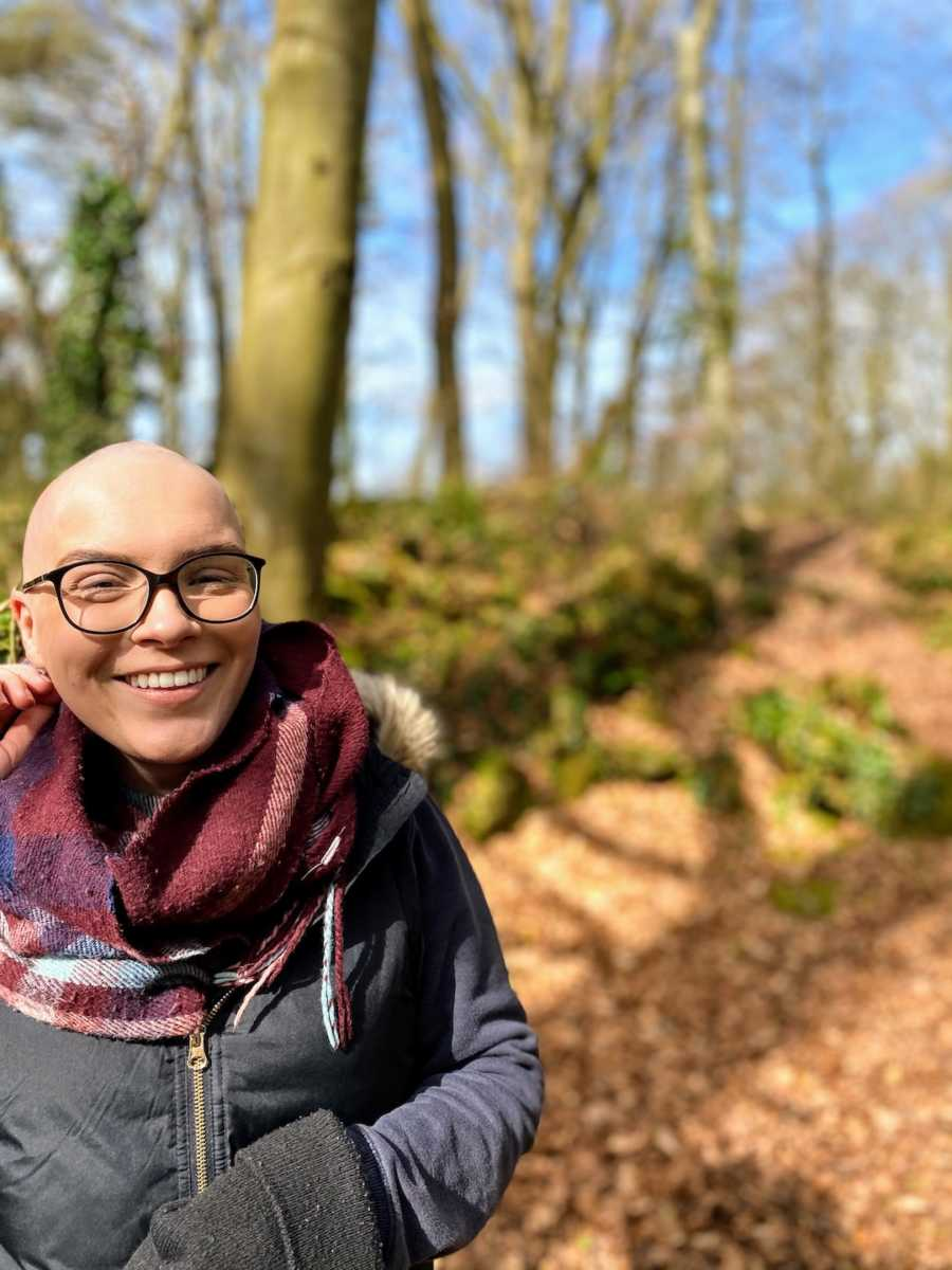 Bald woman wearing scarf and glasses standing in woods