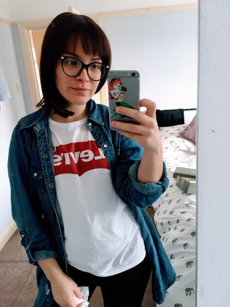 Woman wearing Levi Jeans shirt taking selfie in mirror