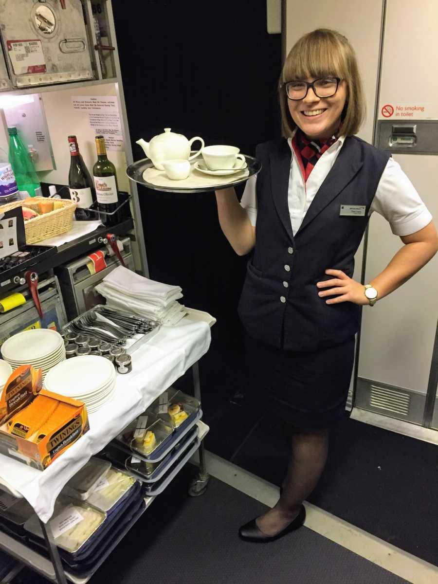Flight attendant holding tea tray on airplane