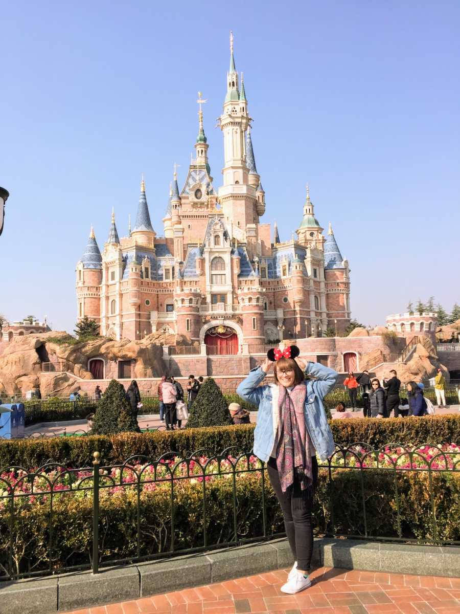 Woman at Disney wearing Mickey Mouse ears posing in front of castle