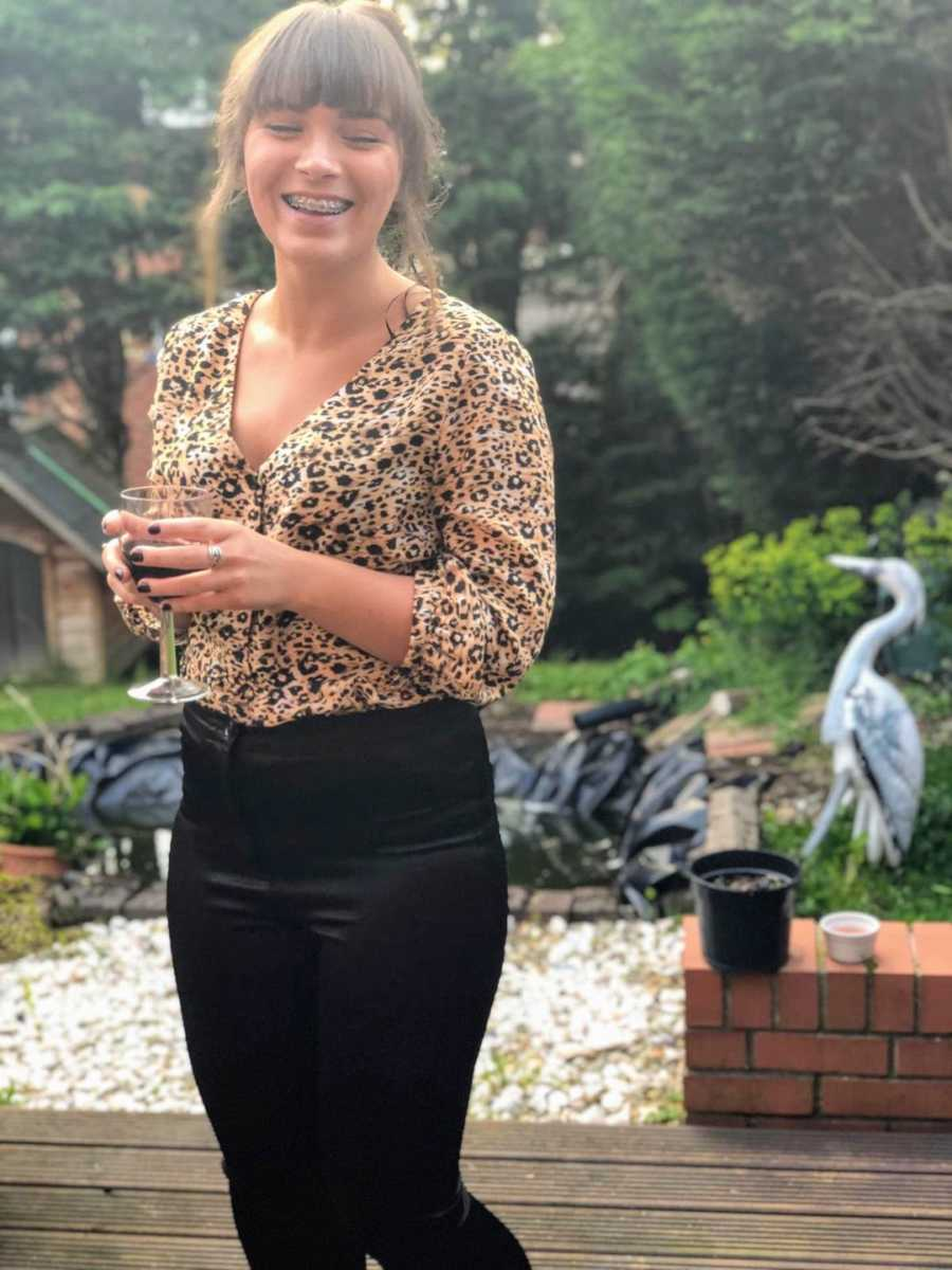 Woman smiling standing outside holding wine glass