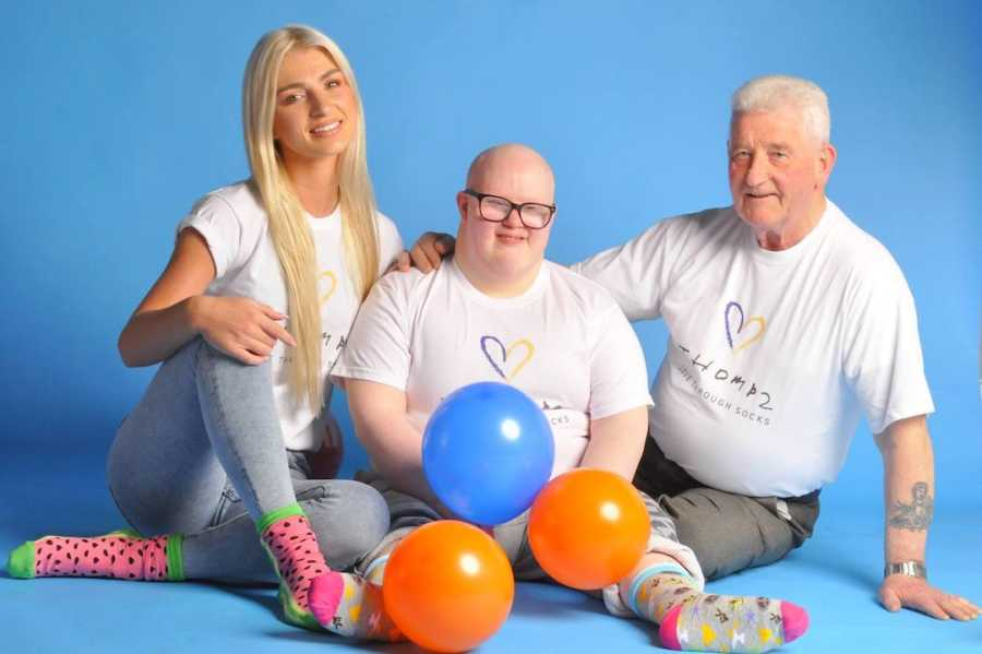 Three people sitting on the floor in front of blue background with balloons