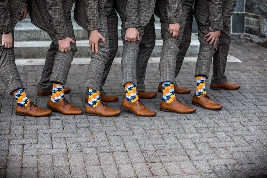 Men pulling up pants to show socks with puzzle pieces